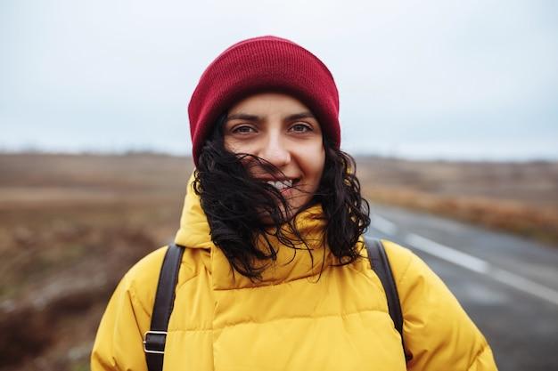 黄色いジャケットと赤い帽子をかぶったバックパックを持った女性観光客の肖像画が道路に立っています。