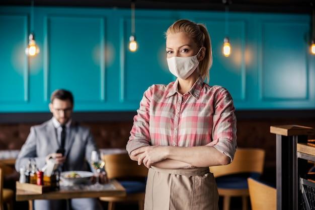 腕を組んでモダンな屋内レストランに立っている女性ウェイトレスの肖像画。