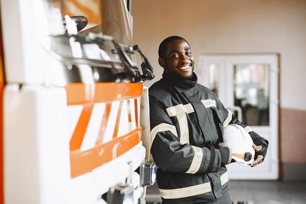 Портрет пожарного, стоящего перед пожарной машиной