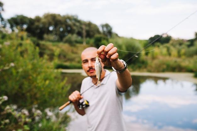 Портрет рыбака, держащего свежую рыбу против озера
