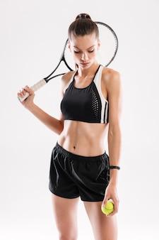 Портрет подходящей женщины в спортивной одежде с теннисной ракеткой