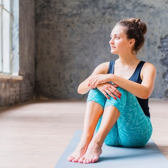Portrait of a fit young woman sitting on exercise mat
