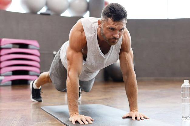 체육관에서 판자 운동을 하는 피트니스 남자의 초상화.
