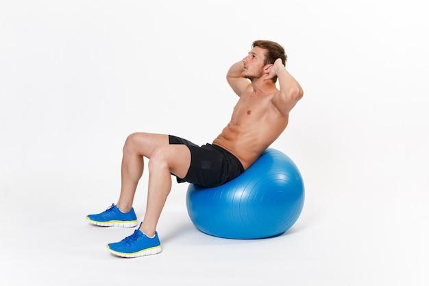ジムボールでストレッチ体操を行うフィットネス男の肖像