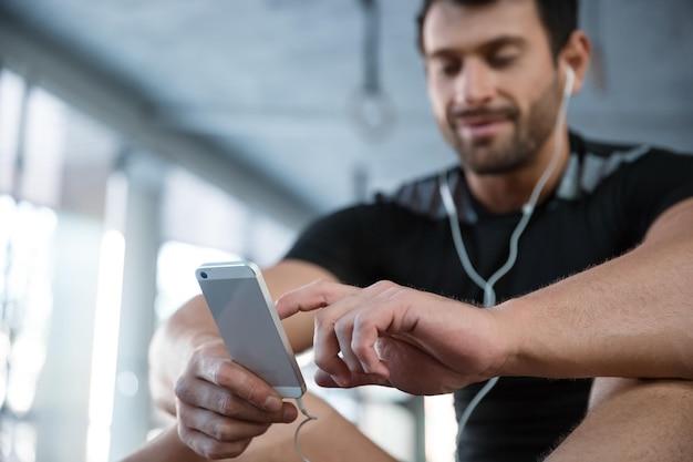 체육관에서 스마트 폰을 사용 하여 피트 니스 남자의 초상화. 스마트 폰에 집중