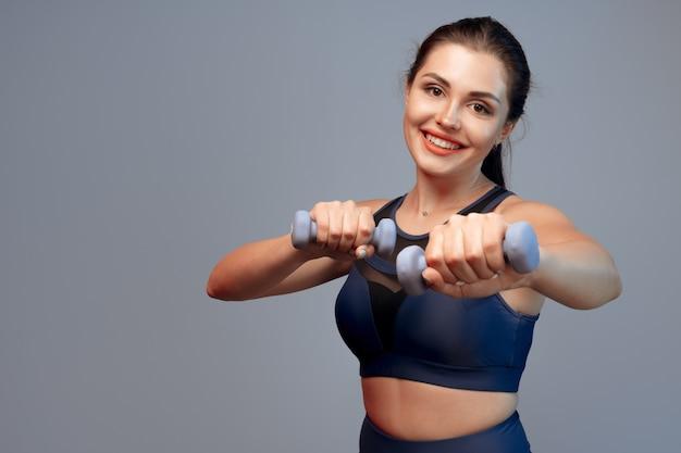 Портрет фитнес-модели, тренирующейся с гантелями на сером фоне