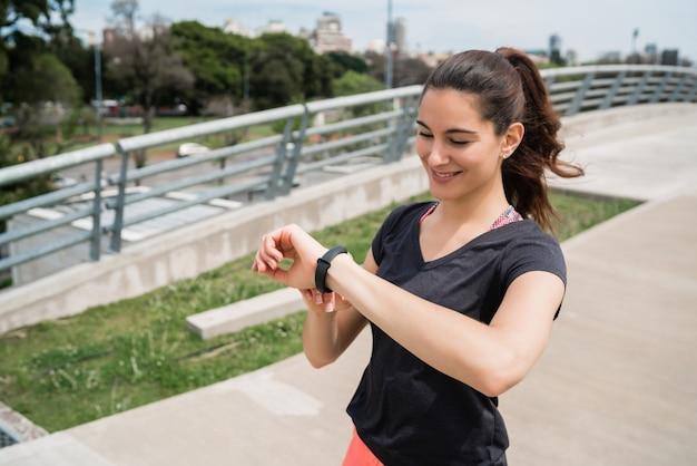 Портрет женщины фитнеса проверяя время на ее умных часах. концепция спорта и здорового образа жизни.