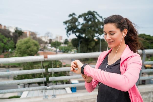 スマートウォッチで時間をチェックするフィットネス女性の肖像画。スポーツと健康的なライフスタイルのコンセプト。