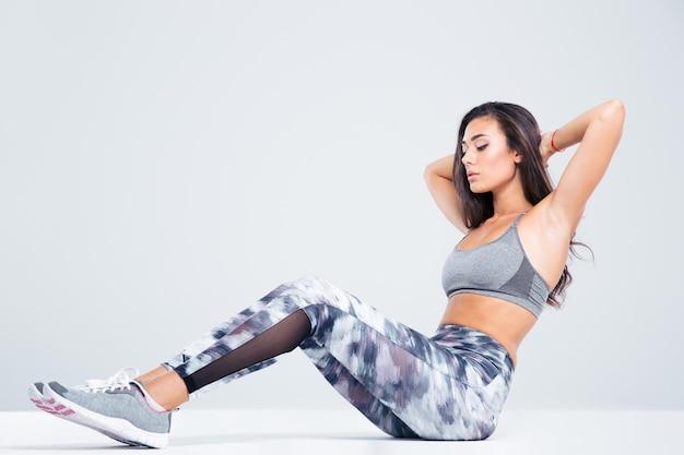 Портрет фитнес-женщины, делающей упражнения на пресс, изолированные на белой стене