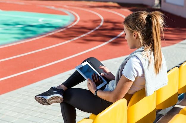 屋外スタジアムでタブレットコンピューターで休んでいるフィットネス女性の肖像画