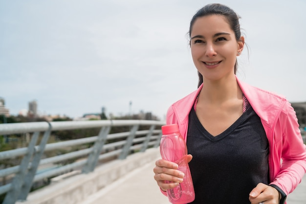 通りで屋外で水のボトルを実行し、保持しているフィットネス女性の肖像画。スポーツと健康的なライフスタイル。