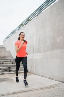 灰色の背景に対して通りを走っているフィットネス女性の肖像画。スポーツと健康的なライフスタイル。