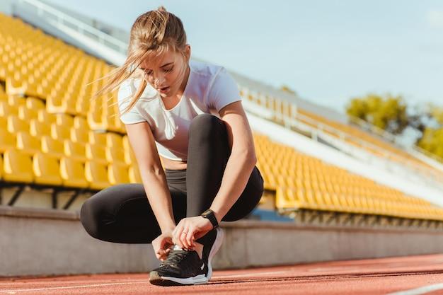 야외 경기장에서 피트니스 여자 넥타이 신발 끈의 초상화