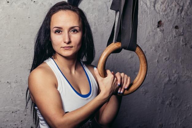 ジムで体操リングとフィットネスwomanトレーニング腕の肖像画