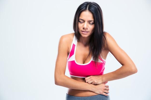 胃の痛みを持つフィットネス女性の肖像画