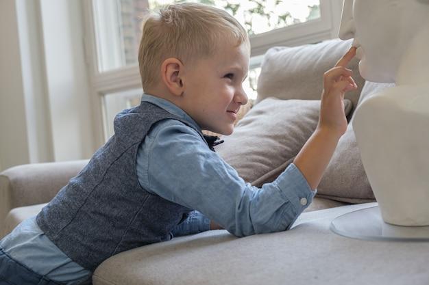 プロフィールの5歳の男の子の肖像画男の子はソファに横たわっている間石膏の胸像に触れます