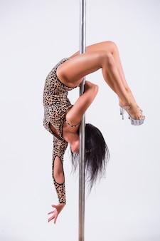 ポールでバランスをとる柔軟な女性ダンサーの肖像画。白い背景で隔離