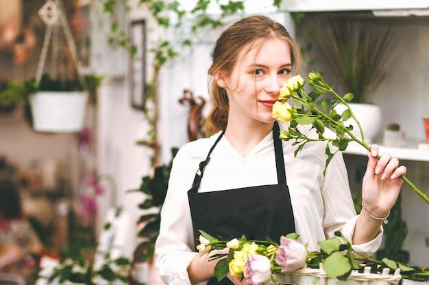 花のブティックで手に花を持つ花屋の少女の肖像画。