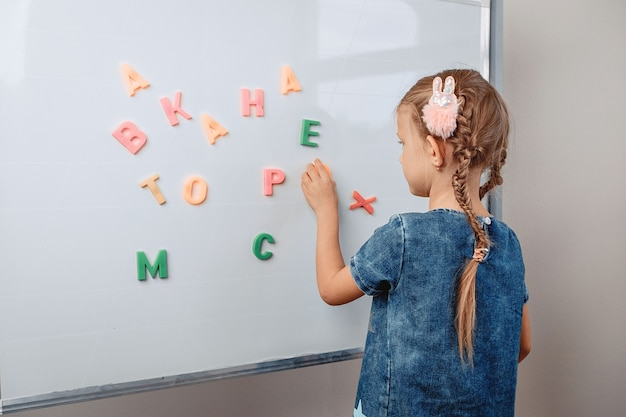 Портрет сосредоточенного умного прекрасного ребенка, стоящего перед белой доской с буквами алфавита в правильном порядке. концепция фокуса