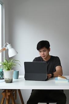 프리랜서 그래픽 디자이너 남자의 초상화는 그의 현대 작업 공간에서 컴퓨터 태블릿에 노력하고 있습니다.