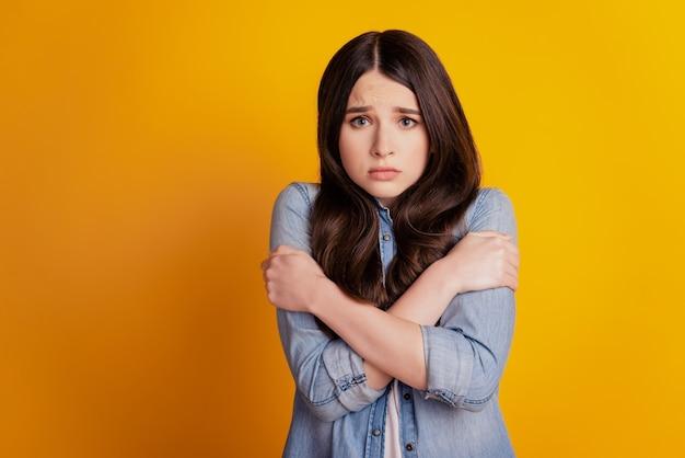 얼어붙은 예쁜 여자의 초상화는 노란 배경에 슬픈 얼굴을 껴안고 어깨를 안고 있다