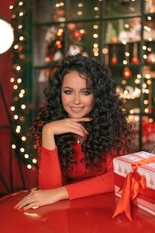 赤い弓でギフトボックスを保持している、フレンドリーでポジティブな笑顔の女性の肖像画。女性はカメラを見ています。ボケ。