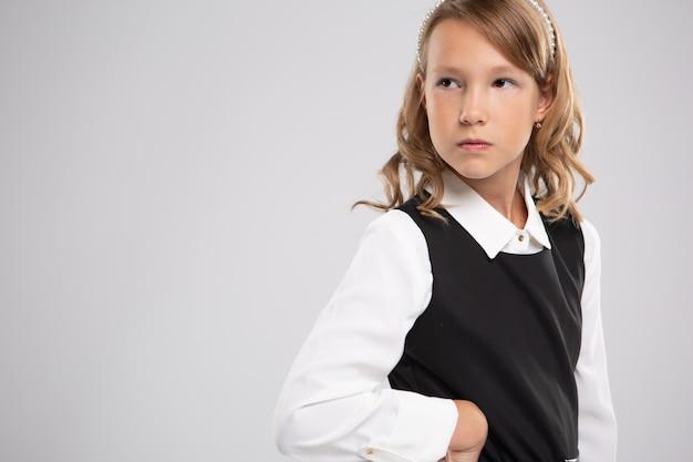 Портрет разочарование школьницы, стоя с ее руки на бедрах и глядя на белую стену