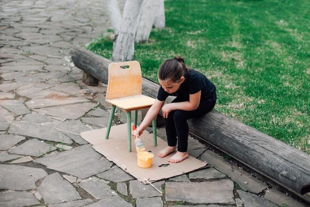 Портрет ребенка в полный рост, рисующего стул для повторного использования и сидящего на бревне на каменной дорожке у ...