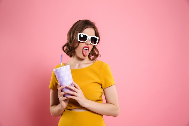 Портрет смешной девушки в солнечных очках, держа чашку