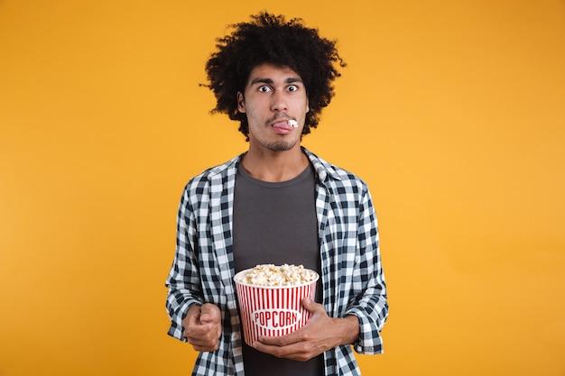 Портрет забавного афроамериканца, едящего попкорн