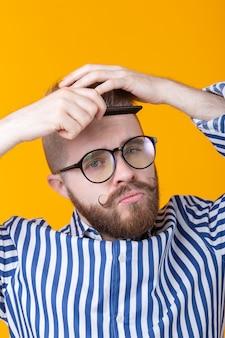 그의 머리를 빗질 콧수염과 수염을 가진 재미있는 잘 생긴 젊은 남성 힙 스터의 초상화