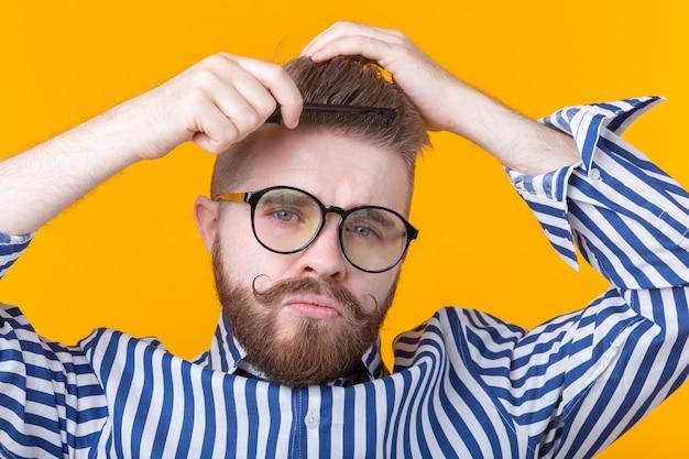 Портрет забавного красивого молодого хипстера мужского пола с усами и бородой, расчесывающего волосы