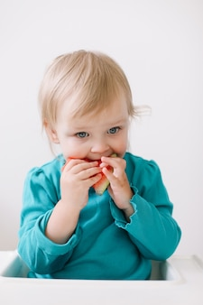 高い椅子に座ってスイカを食べる面白い小さな女の赤ちゃんの肖像画