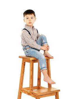 孤立した高いスツールに裸足で座っている面白い小さな男の子の肖像画