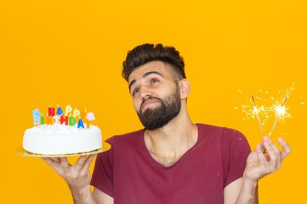 노란색 배경에 손에 축하 수제 케이크를 들고 있는 재미있는 긍정적인 남자의 초상화. 개념과 재미와 축하.