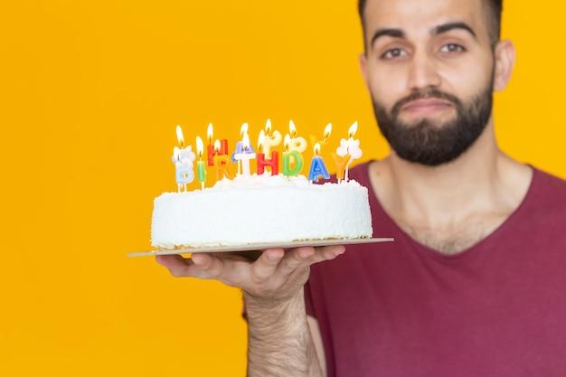 노란색에 손에 축하 홈메이드 케이크를 들고 있는 재미있는 긍정적인 남자의 초상화
