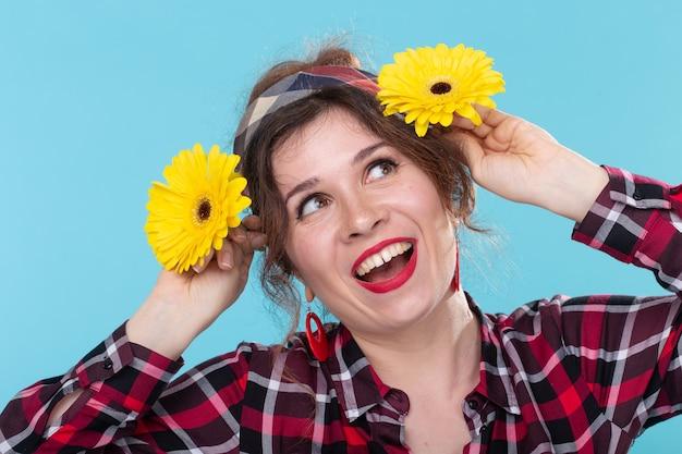 파란색 표면에 포즈를 취하는 그녀의 머리에 노란색 꽃을 대체하는 빨간색 체크 무늬 셔츠에 재미 있은 미소 예쁜 젊은 여자의 초상화