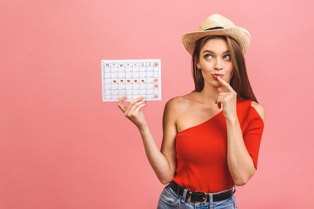 Портрет забавной молодой девушки, держащей календарь периодов, изолированные на розовом фоне