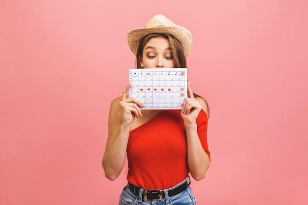 Портрет забавной молодой девушки в летней шляпе, прячущейся за календарём периодов, изолированным на розовом фоне