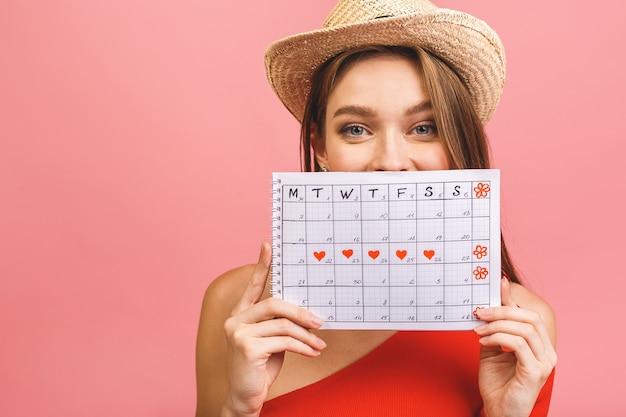 Портрет забавной молодой девушки в летней шляпе, прячущейся за календарём периодов
