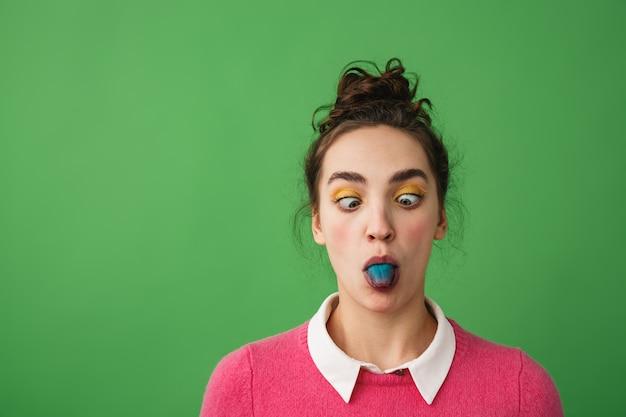 Портрет забавной молодой девушки, стоящей изолированно, показывая синий язык