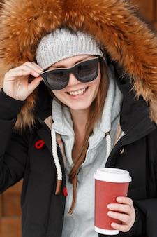 그녀의 손에 커피 한잔과 함께 모피 후드와 함께 따뜻한 세련 된 재킷에 니트 모자에 선글라스에 아름 다운 미소와 함께 재미있는 젊은 여자 hipster의 초상화. 쾌활한 유행 소녀.