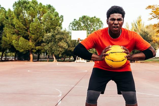 反抗的な表情と彼の手にバスケットボールを持つ猛烈な黒のアフロ少年の肖像画。ゲームをプレイする準備ができました。