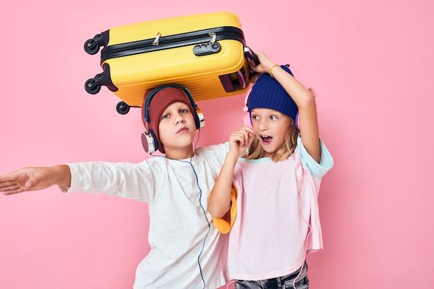 休日の準備をしている女の子と男の子の肖像画若い旅行者ピンク色の背景
