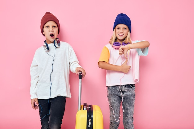 彼の手のスタジオでポーズをとって黄色のスーツケースを持つ少女と少年の肖像画