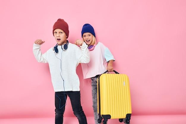 ヘッドフォンスタジオポーズで女の子と男の子の黄色いスーツケースの肖像画