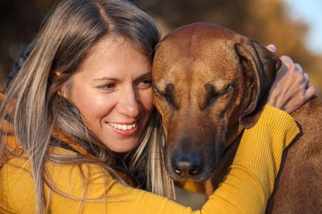 少女とローデシアン・リッジバックの肖像画。犬は目を閉じた。黄色の背景