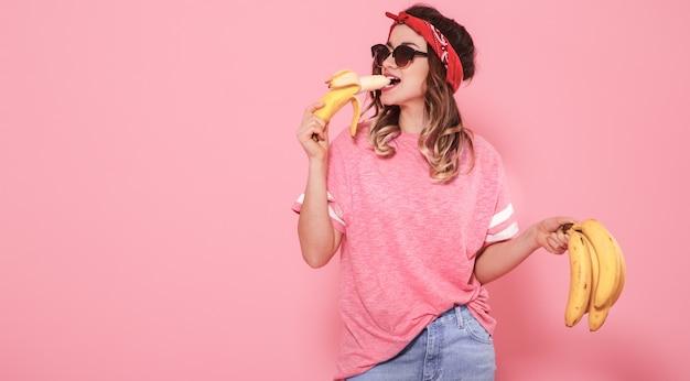 Портрет девушки и бананы, изолированные на розовой стене