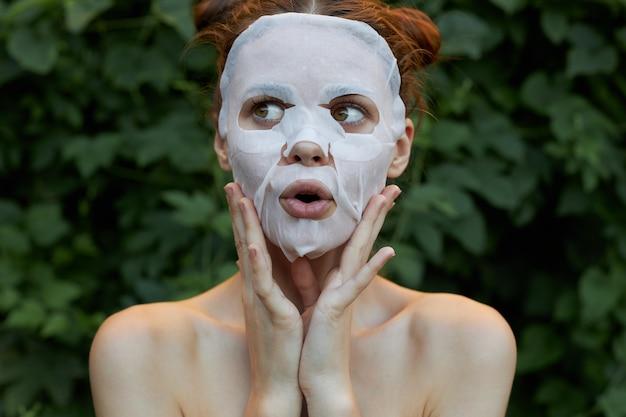女の子のフェイスマスクのポートレート手で顔を触る透明肌