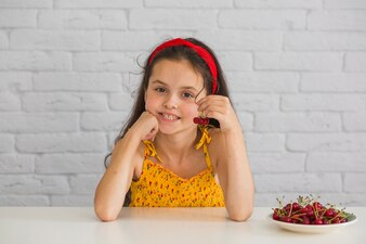 Portrait of a girl holding red cherries on plate